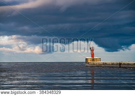 Orange Port Lighthouse. The Gate Of The Port In Liepaja, Latvia. Pier Covered With Snow. Seagulls On