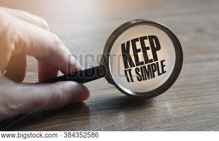 Hand Holding Magnifying Glass With Word Keep It Simple. Education And Business Concept