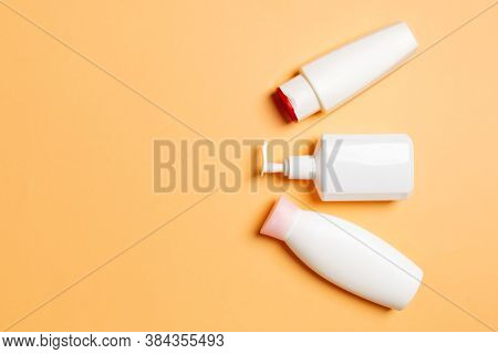 Set Of White Cosmetic Containers Isolated On Colored Background, Top View With Copy Space. Group Of