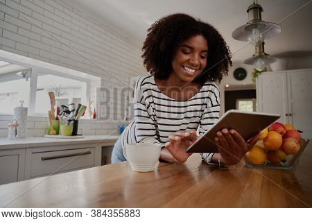 African American Woman Standing In Kitchen Leaning On Counter Using Digital Tablet Looking At Online