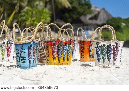 Colored Wicker Woman Bags In Typical Zanzibar Style On The White Sandy Beach Near Turquoise Ocean Of