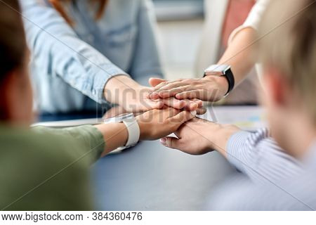 cooperation, corporate and team work concept - close up of business team stacking hands at office
