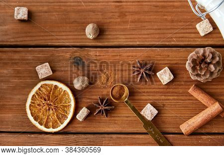 christmas and seasonal drinks concept - aromatic spices, brown sugar, nutmeg and pine cone on wooden background