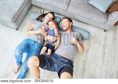 Happy family with toddler lying on pillows in front of sofa in living room