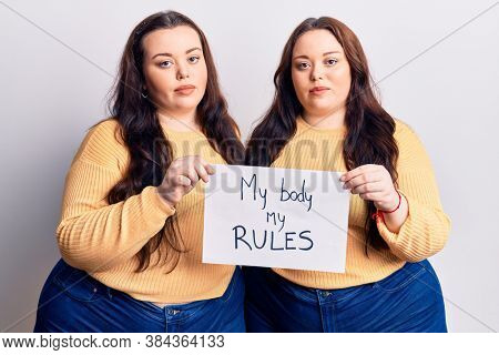 Young plus size twins holding my body my rules banner thinking attitude and sober expression looking self confident
