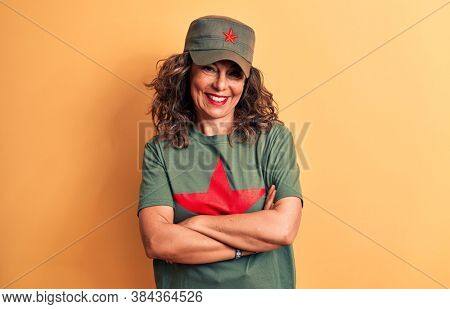 Middle age brunette woman wearing t-shirt and cap with red star symbol of communism happy face smiling with crossed arms looking at the camera. Positive person.