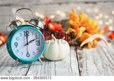 Set Your Clocks And Fall Back. Clock And Decorations Of Mini Pumpkins, Colorful Autumn Leaves, Antle