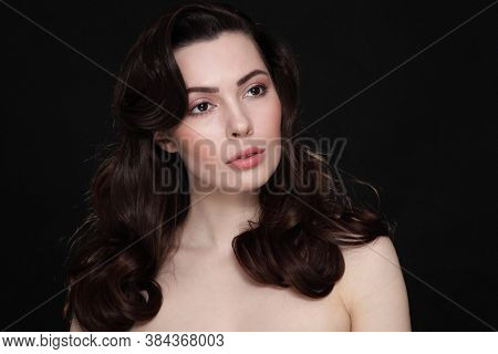 Young beautiful brunette with long curly hair and nude makeup