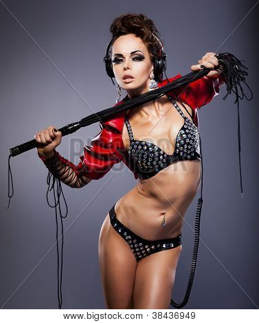 Young Sexy Woman Mistress In Headphones And Whip In Erotic Pose