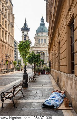 Budapest, Hungary - August 25, 2019: An unidentified homeless man sleeps on the sidewalk of the street in Budapest center. St. Stephen's Basilica Roman Catholic cathedrals at background.