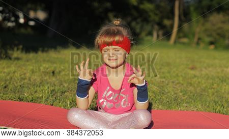 Child In Pink Sportswear Sitting On Mat And Performing Yoga Meditation Breathing Technique Outdoors