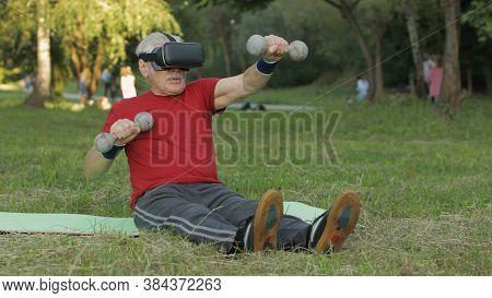 Elderly Man In Vr Headset Helmet Making Fitness Exercises With Dumbbells Outdoors. Online Sport Work