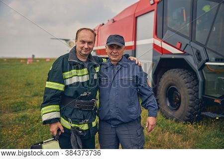 Two Men From Fire Brigade Looking At The Photo Camera