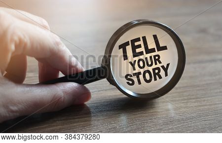 Tell Your Story Under Magnifying Glass In Hand On Wooden Table. Business Concept