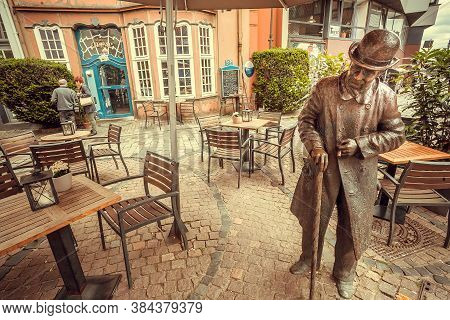 Bremen, Germany: Local Cafe, Restaurants And Sculpture Of Walking Pedestrian On Narrow Street Of Old