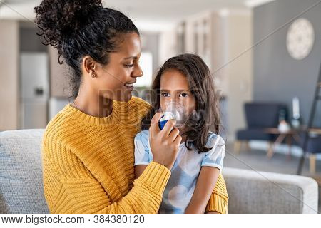 Little indian girl making inhalation with nebulizer with lovely mother. Woman makes inhalation to a sick child while embracing her. Mom helping daughter with cold and flu to inahale nebuliser aerosol.