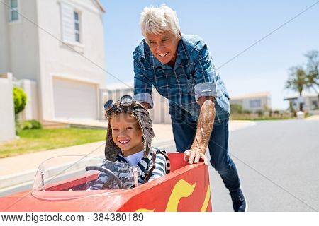 Grandfather helping grandson ride on kid toy car outdoor. Senior man pushing child gokart while wearing pilot helmet on lane. Old granddad playing with grandchild riding toy race car on walkway.