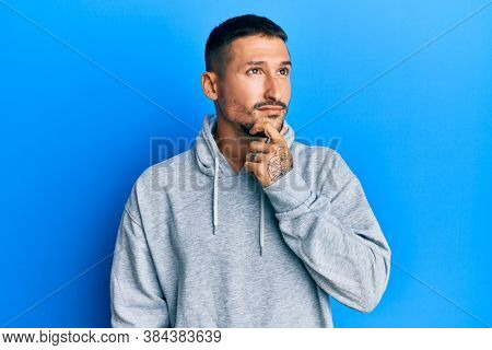 Handsome man with tattoos wearing casual sweatshirt thinking concentrated about doubt with finger on chin and looking up wondering