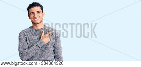 Hispanic handsome young man wearing casual sweater cheerful with a smile of face pointing with hand and finger up to the side with happy and natural expression on face