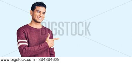 Hispanic handsome young man wearing casual clothes cheerful with a smile of face pointing with hand and finger up to the side with happy and natural expression on face
