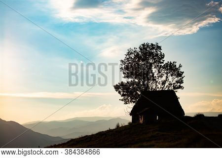 Silhouette of small wooden cottage in Transylvanian mountains agains sunset sky.