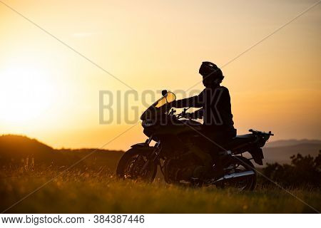 Silhouette of young motorcycle rider on the road with sunset light background.
