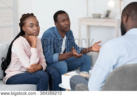 Emotional African Man Complaining About Family Problems With His Wife At Couple Therapy Session, Sit