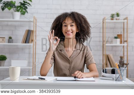 Great Freelance Job At Home In Self-isolation. African American Girl At Workspace Shows Okay Sign An