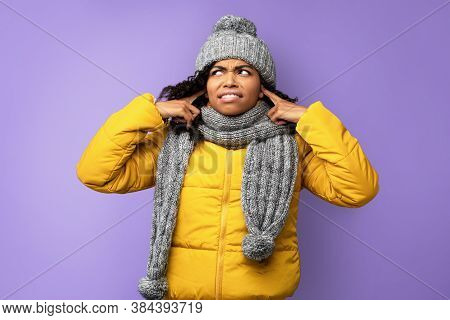 Noise Concept. Discontented African Woman In Winter Clothes Plugging Ears With Her Fingers Posing On