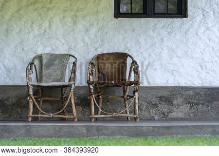 Two Rattan Chairs Covered With Skin Near The White Wall Of The House. Tanzania, East Africa