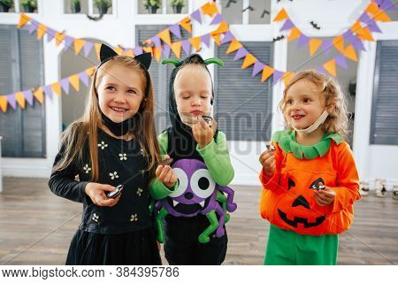 Children's Trick Or Treat In A Halloween Costume And Face Masks Eat Treats And Have Fun Laughing. Ch