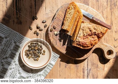 Homemade Baked Pumpkin Bread Loaf With Knife On Cutting Board And Plate With Seeds On Rustic Table.