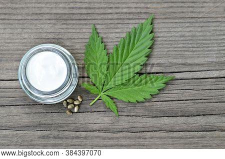 Cannabis Cream In A Jar With Marijuana Leaf And Seeds On Wooden Background.cbd Cosmetics,hemp Extrac