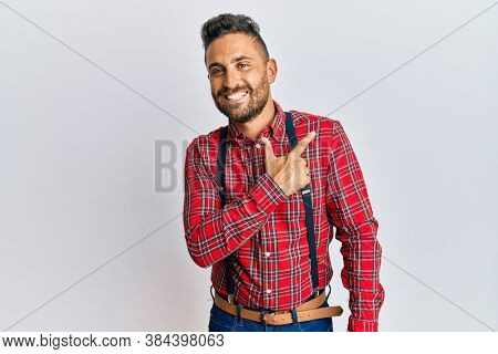 Handsome man with beard wearing hipster elegant look cheerful with a smile of face pointing with hand and finger up to the side with happy and natural expression on face
