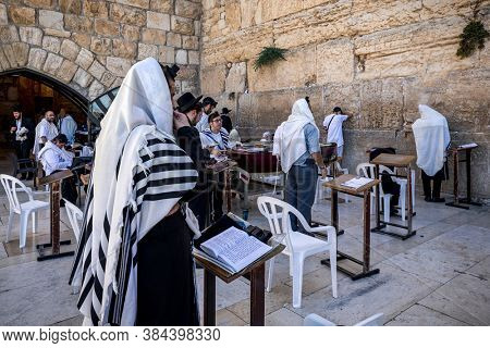 JERUSALEM, ISRAEL - JULY 14, 2019: Group of orthodox Jews praying at Western Wall in Old City of Jerusalem - aka Wailing Wall or Kotel, sacred place in Judaism.