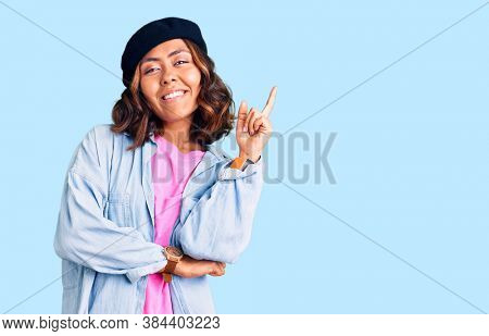 Young beautiful mixed race woman wearing french look with beret with a big smile on face, pointing with hand and finger to the side looking at the camera.