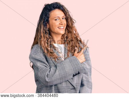 Young hispanic woman with tattoo wearing business oversize jacket cheerful with a smile of face pointing with hand and finger up to the side with happy and natural expression on face
