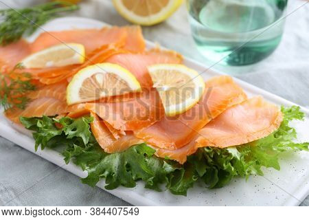 Slices of smoked salmon with lettuce and sliced lemon on a cutting board. Selective focus on the front edge of fish slices