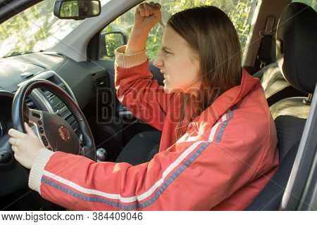Angry Young Woman Driver With Red Hair Threatens Other Drivers With A Fist. Traffic Jams Concept. St