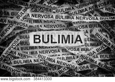 Bulimia. Torn Pieces Of Paper With The Word Bulimia. Concept Image. Black And White. Close Up.