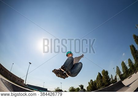 Boy With Inline Skates, Rollerblade, Doing A Jump In A Skate Park