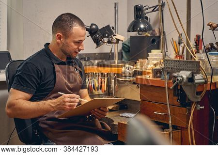 Smiling Young Man Sitting At The Workbench