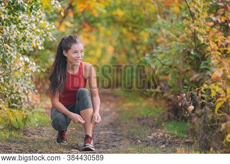 Autumn outdoor exercise lifestyle. Asian runner woman tying running shoes ready to run for fitness cardio workout in forest nature.