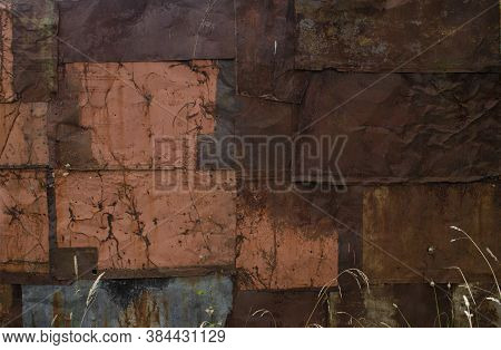 Dry Grass Near The Rust And Oxidized Wall. Old Iron Panel. The Wall Of Rusted Plates. Grunge Rusted