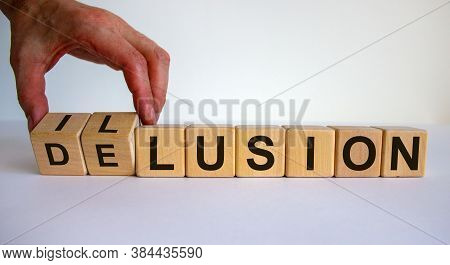 Hand Turns A Cube And Changes The Word Delusion To Illusion. Beautiful White Background. Business Co