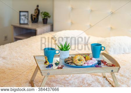Close-up Of Tray With Breakfast On The Bed. Romantic Composition. Couple Of Mugs, Sweets And Donut.