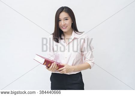 Portrait Of Beautiful Woman Student In Pink Shirt Is Holding A Book Isolated Over White Background S