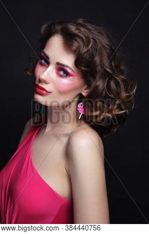 Portrait of young beautiful girl with curly hair and pink  makeup