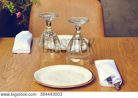 Table On The Veranda Of The Restaurant, Served For Two: Two Inverted Glasses, Napkins And Cutlery On
