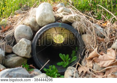 Looking Through A French Drain With A Black Pipe And Large Rocks Surrounding It